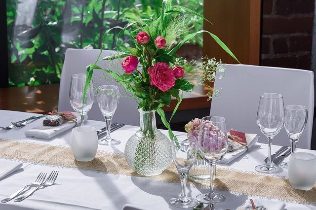 A glass of wine and a vase of flowers on a table